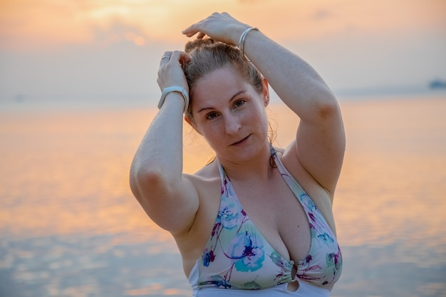 Piękna młoda kobieta na tle zachodu słońca nad morzem