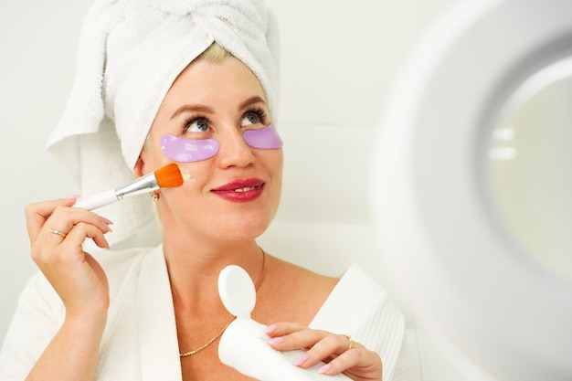 Piękna młoda kobieta nakłada kosmetyki organiczne na swoją skórę