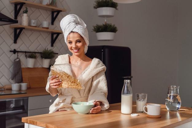 Piękna młoda kobieta nalewa płatki kukurydziane w talerzu z mlekiem. rano dziewczyna ma zdrowe śniadanie w stylowej, przytulnej kuchni.