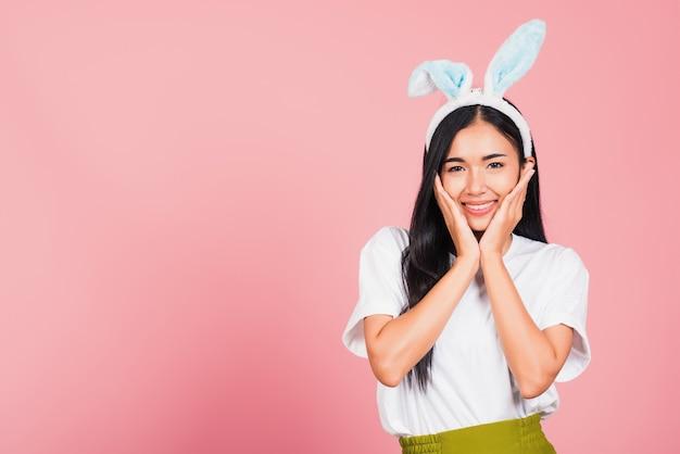 Piękna młoda kobieta nastolatka uśmiechnięta sobie uszy królika wielkanocnego, trzymając jej policzki podekscytowany zaskoczony