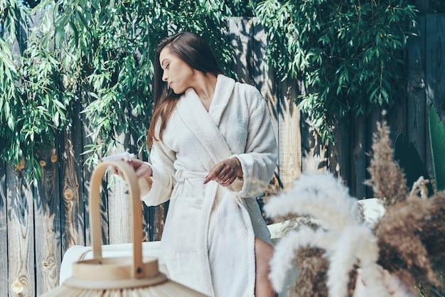 Piękna młoda kobieta nawilżający krem do rąk, opierając się o wannę na zewnątrz outdoor