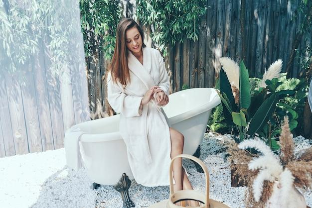 Piękna młoda kobieta nawilżający krem, opierając się na wannie na zewnątrz
