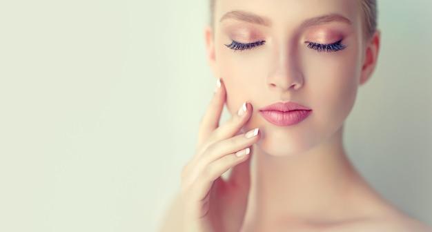 Piękna, młoda kobieta o czystej, świeżej skórze, delikatnym makijażu i różowej szmince na ustach dotyka twarzy.