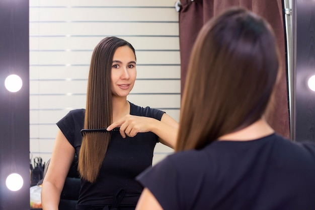 Piękna młoda kobieta o długich, gładkich brązowych włosach dba o swoje włosy. czesała włosy i patrzyła w lustro