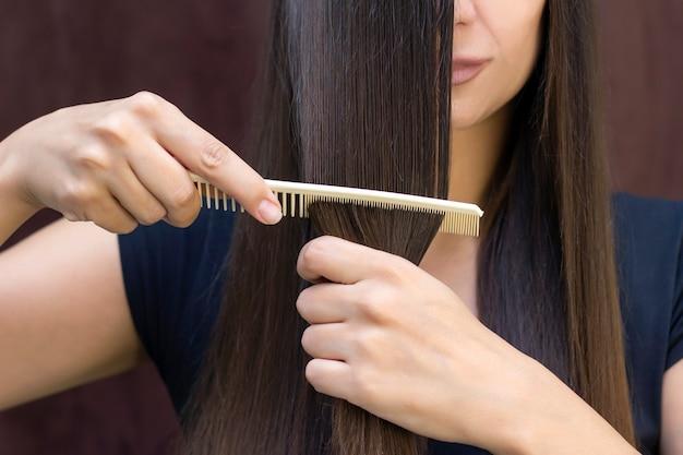 Piękna młoda kobieta o długich, gładkich brązowych włosach dba o swoje włosy.