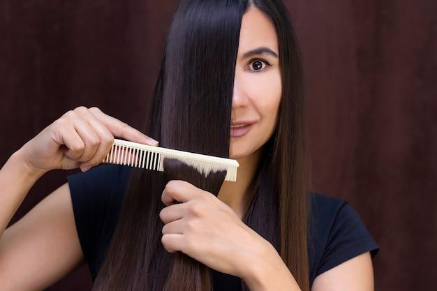 Piękna młoda kobieta o długich, gładkich brązowych włosach dba o włosy
