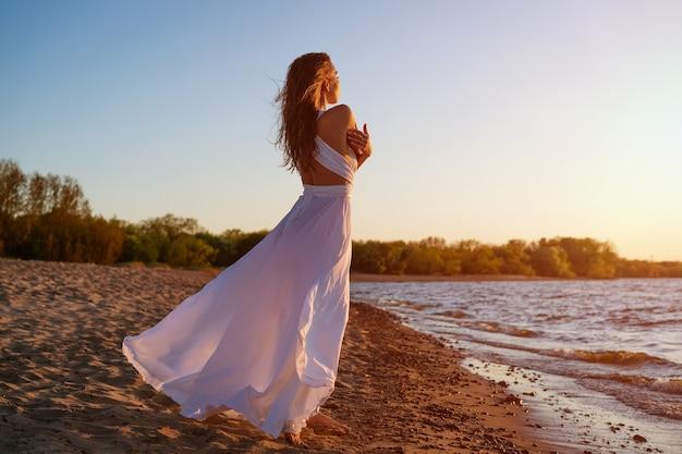 Piękna młoda kobieta o kaukaskim wyglądzie z farbowanymi włosami pozuje nad brzegiem morza w słońcu o zachodzie słońca w białej sukni na wietrze romantyczna szczupła dziewczyna w przyrodzie cieszy się relaksem
