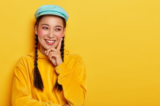 Piękna młoda kobieta o wschodnim wyglądzie, dotyka różowego policzka palcem wskazującym, patrzy na bok, ma zębaty uśmiech, ubrana w jasny aksamitny sweter z kapturem