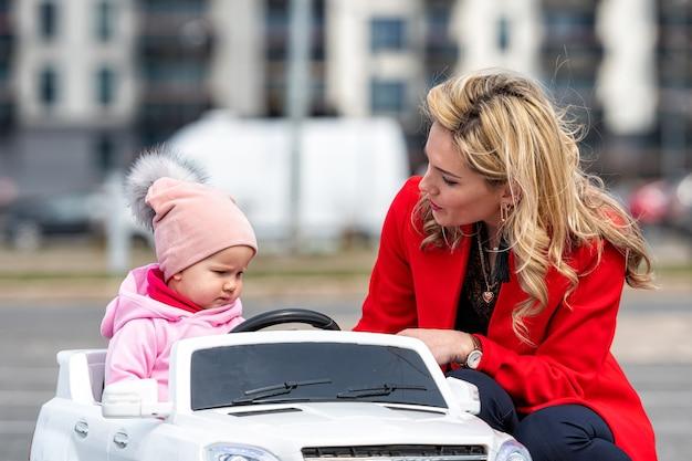 Piękna młoda kobieta obok córki w biały samochód elektryczny dla dzieci na parkingu