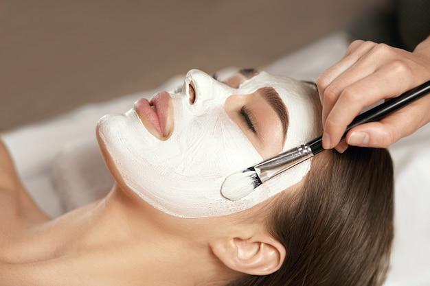 Piękna młoda kobieta odbiera białą maseczkę na twarz w gabinecie kosmetycznym. spa do pielęgnacji skóry i ciała. zabieg upiększający na twarz.