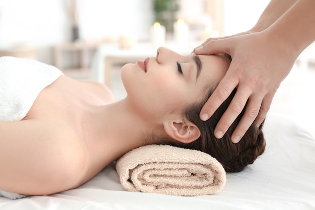 Piękna młoda kobieta odbiera masaż twarzy w salonie spa