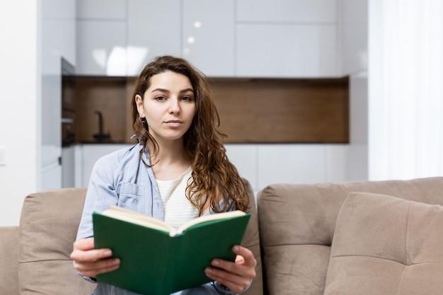 Piękna młoda kobieta, odpoczynek w domu, siedząc na kanapie i czytając ciekawą książkę