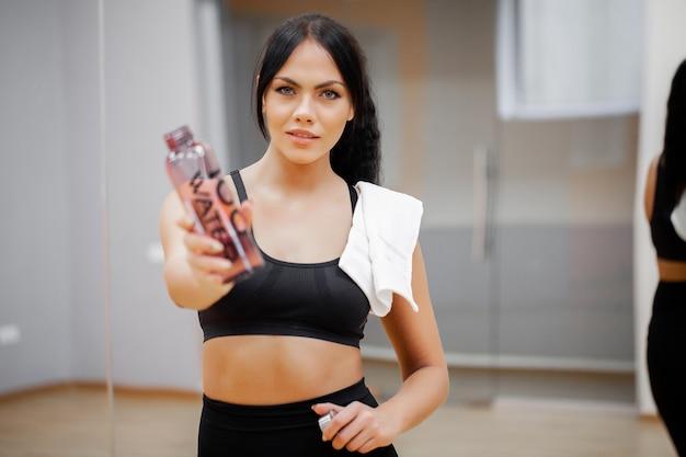 Piękna młoda kobieta odpoczynku i wody pitnej na siłowni.