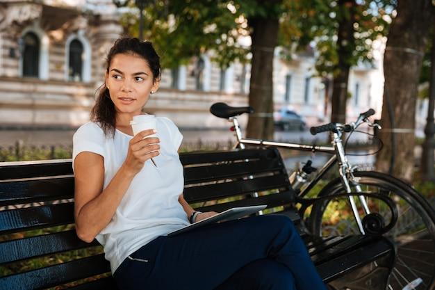 Piękna młoda kobieta odpoczywa na ławce z filiżanką kawy w parku miejskim