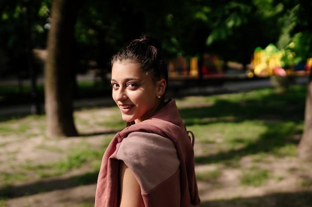 Piękna młoda kobieta odpoczywa po joggingu w parku.