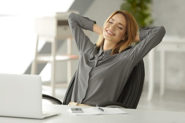 Piękna młoda kobieta odpoczywa w miejscu pracy w biurze