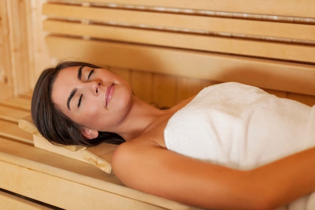 Piękna młoda kobieta odpoczywa w saunie