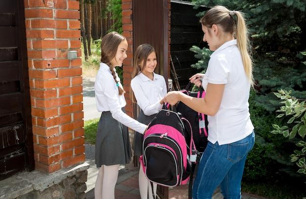 Piękna młoda kobieta odprowadzająca córki do szkoły o poranku