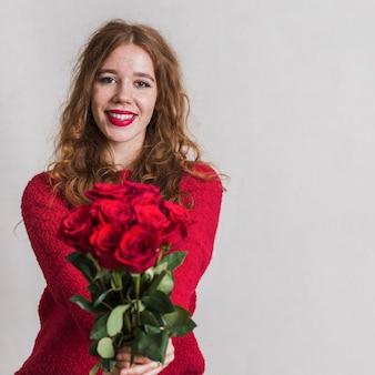 Piękna młoda kobieta oferuje bukiet róż