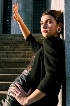 Piękna młoda kobieta opiera się na ścianie osłaniając oczy przed słońcem