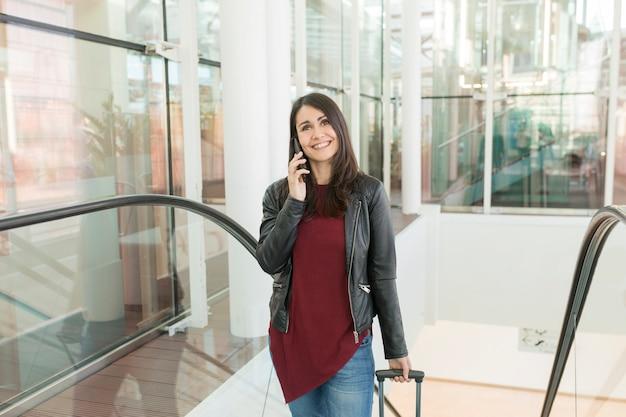 Piękna młoda kobieta opowiada na jej telefonie komórkowym i ono uśmiecha się. koncepcja podróży na lotnisko, ona idzie po schodach wózkiem. dzień i styl życia