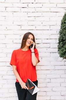 Piękna młoda kobieta opowiada na telefonie komórkowym przed ściana z cegieł