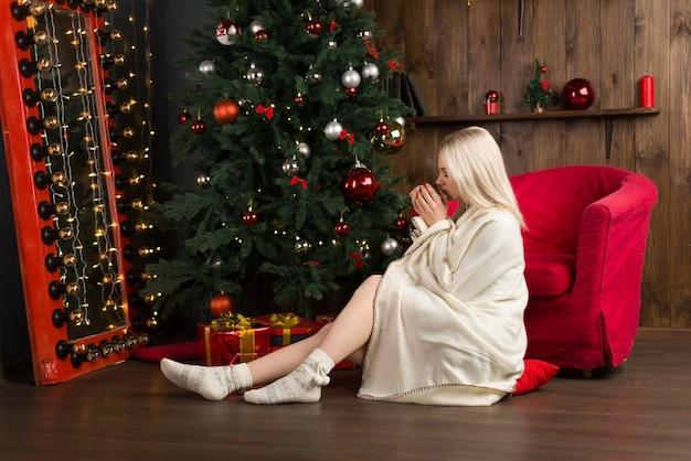 Piękna młoda kobieta owinięta w kratę siedzi na czerwonym krześle z filiżanką herbaty lub kawy w noworocznym wnętrzu domu w pobliżu choinki. - obraz