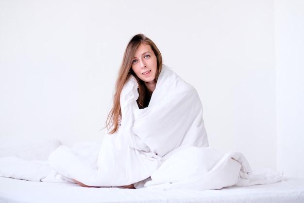 Piękna młoda kobieta owinięta w miękki koc siedzi w domu. zimowa atmosfera. zaspałem do pracy. dziewczyna zachorowała. sezon grzewczy