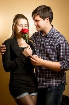 Piękna młoda kobieta pachnąca czerwoną różą przedstawiona przez młodego mężczyznę