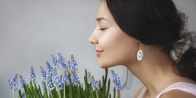 Piękna młoda kobieta pachnący bukiet wiosennych kwiatów z zamkniętymi oczami