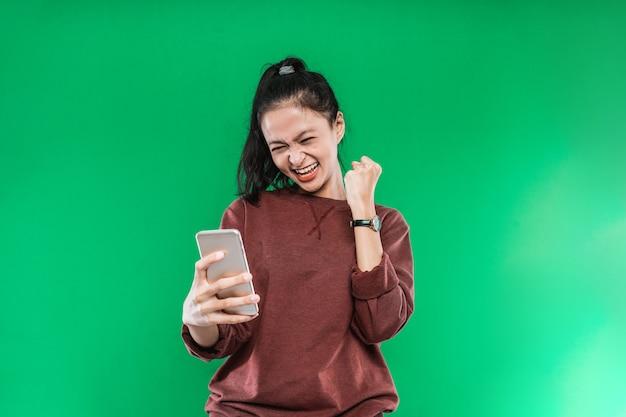 Piękna młoda kobieta patrząc na coś na telefon komórkowy ze szczęśliwym wyrazem twarzy na zielonym tle