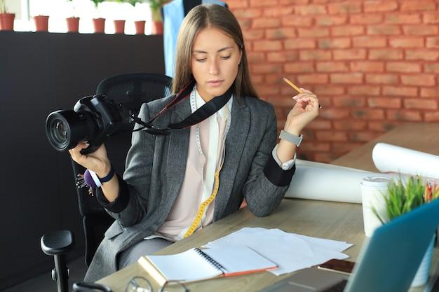 Piękna młoda kobieta, patrząc na swoje notatki i trzymając aparat cyfrowy, siedząc w swoim warsztacie.
