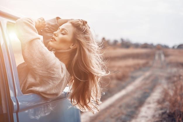 Piękna młoda kobieta patrząc przez okno podczas podróży samochodem w minivanie