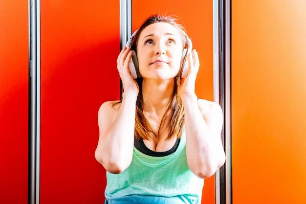 Piękna młoda kobieta, patrząc w górę, odpoczywając, słuchając muzyki w słuchawkach