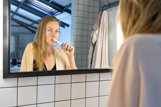 Piękna młoda kobieta, patrząc w lustro w łazience, myje zęby szczoteczką do zębów