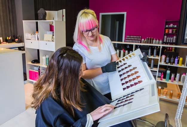 Piękna młoda kobieta patrząca z fryzjerem na paletę farb do włosów, aby zmienić kolor włosów
