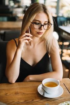 Piękna młoda kobieta patrzeje herbacianą filiżankę opowiada na telefonie komórkowym