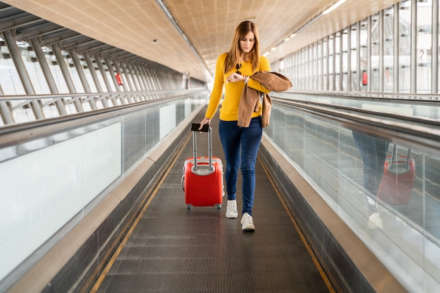 Piękna młoda kobieta patrzeje jej zegarek na lotnisku lub staci z jej bagażem