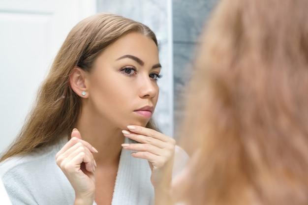 Piękna młoda kobieta patrzy na jej twarz w lustrze
