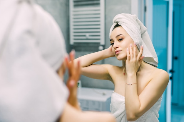 Piękna młoda kobieta patrzy w lustro do masażu twarzy, stosując krem w łazience