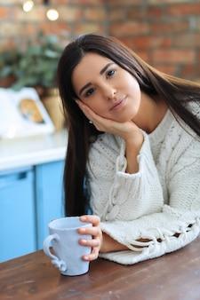 Piękna młoda kobieta picia kawy lub herbaty w kuchni