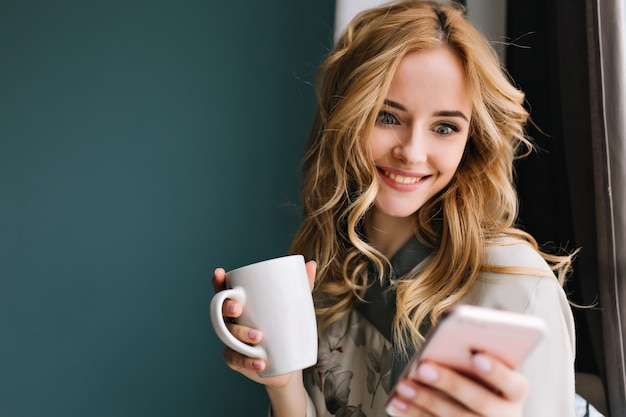Piękna młoda kobieta pijąca rano herbatę lub kawę, trzymając w ręku smartfon, otrzymała ekscytujący komunikat, entuzjastycznie patrząc na telefon. ubrana w ładną piżamę.