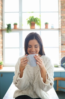 Piękna młoda kobieta pije gorący napój w kuchni