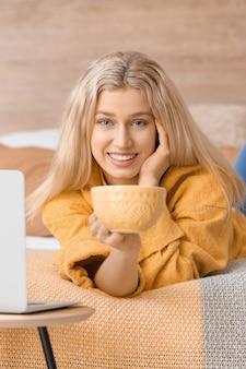 Piękna młoda kobieta pije herbatę w domu
