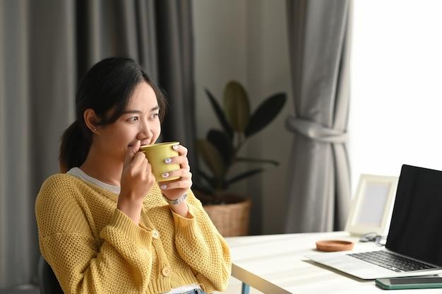 Piękna młoda kobieta pije kawę i patrząc przez okno, siedząc w biurze