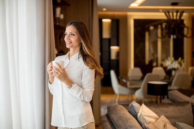 Piękna młoda kobieta pije kawę i patrzeje przez okno podczas gdy stojący w mieszkaniu