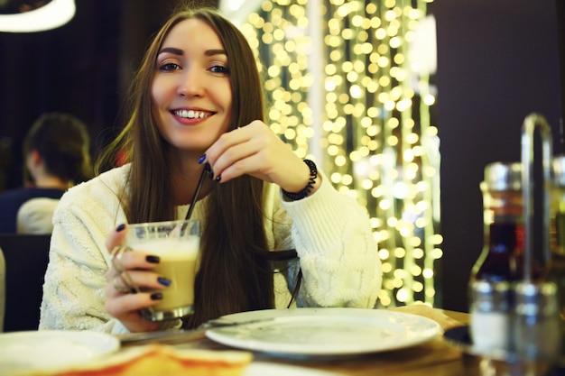 Piękna młoda kobieta pije kawę przy kawiarnią. tonned