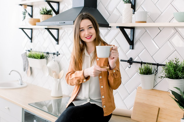 Piękna młoda kobieta pije kawę w kuchni