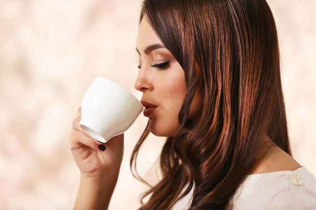 Piękna młoda kobieta pije kawę