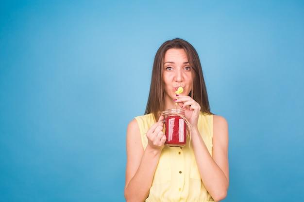 Piękna młoda kobieta pije koktajl truskawkowy na niebiesko. koncepcja zdrowych napojów ekologicznych. osoby na diecie.